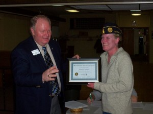 Bruce Holzschuh, veterans affairs coordinator, presenting a certificate of appreciation to Master Sergeant (Ret) Thallassa Gunelius, representing the Bayport American Legion, for the donation of service flags to Metropolitan State's Veterans Center.
