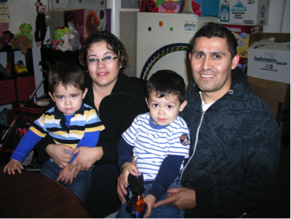 Mayra and Jose Garcia sitting at a table and smiling while holding their two sons, Ivan and Alan.