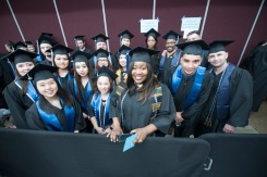A group of graduates smiling at the camera while waiting for commencement to begin.